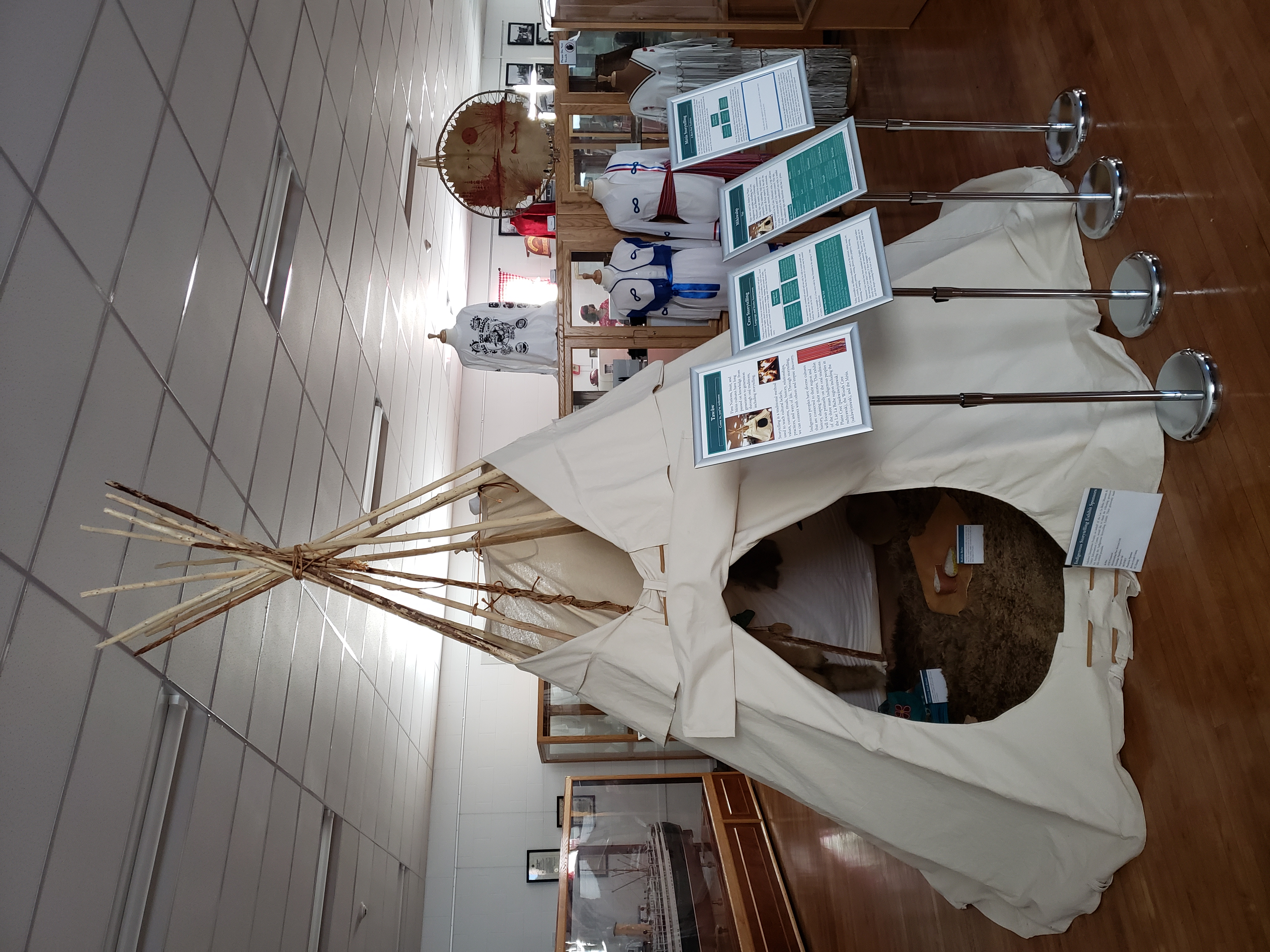 A tipi in a museum with four text panels standing in front of it